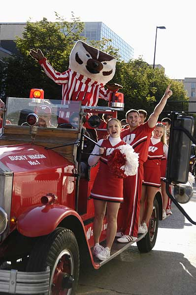 Traveling in the Bucky Wagon around the Dane County Farmers' Market on the capitol square in downtown Madison, mascot Bucky Badger and members of the cheerleading spirit squad share their enthusiasm on a football Saturday game day. At the wheel, Becci Menghini, senior director of campus relations for the Wisconsin Alumni Association, is one of two official drivers for the vintage vehicle. The 1932 American LaFrance fire engine was donated to the university in the mid-1970s by class of 1949 alums J.J. and Norma Normington of Wisconsin Rapids.